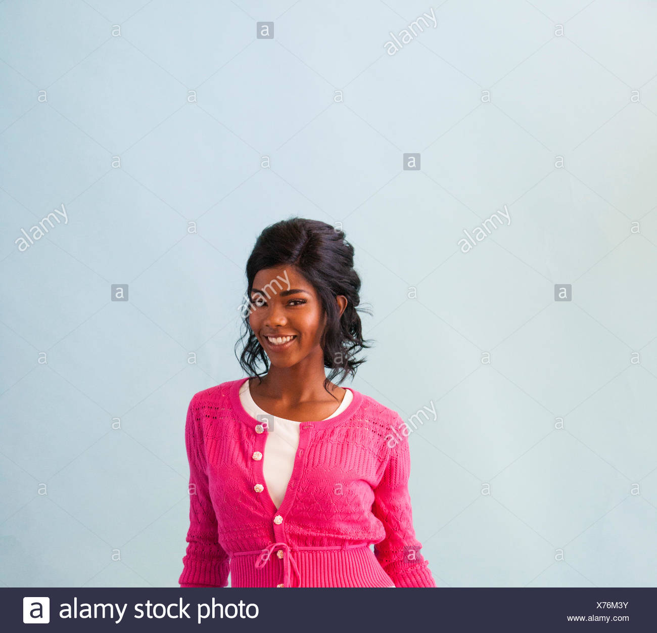 Studio portrait of smiling mid adult woman wearing pink cardigan - Stock Image