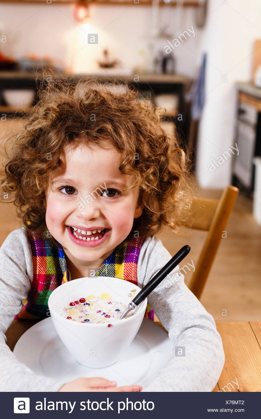 Portrait of girl with toothy grin having cereal in kitchen - Stock Image