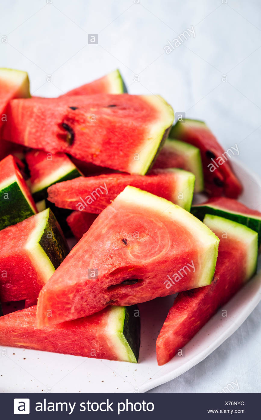 Mini watermelon slices in triangle shape are piled on a plate. - Stock Image