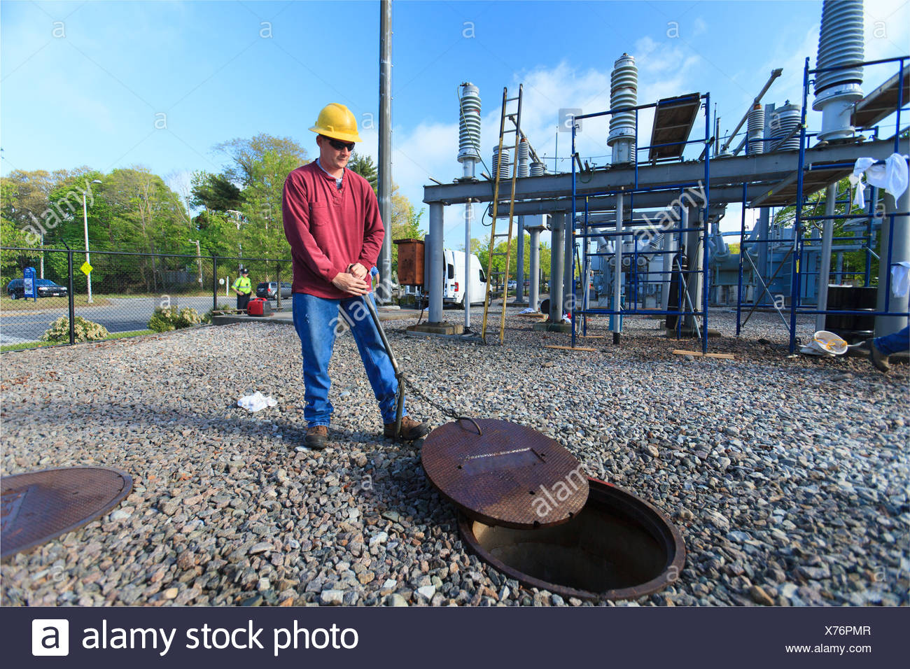Power engineer accessing manhole cover at high voltage power distribution station, Braintree, Massachusetts, USA - Stock Image