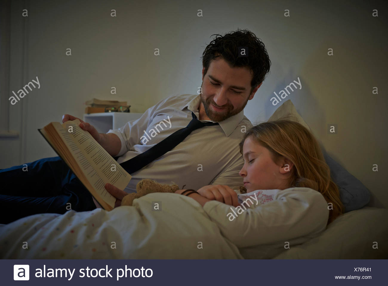 Businessman reading storybook to sleeping daughter at bedtime - Stock Image