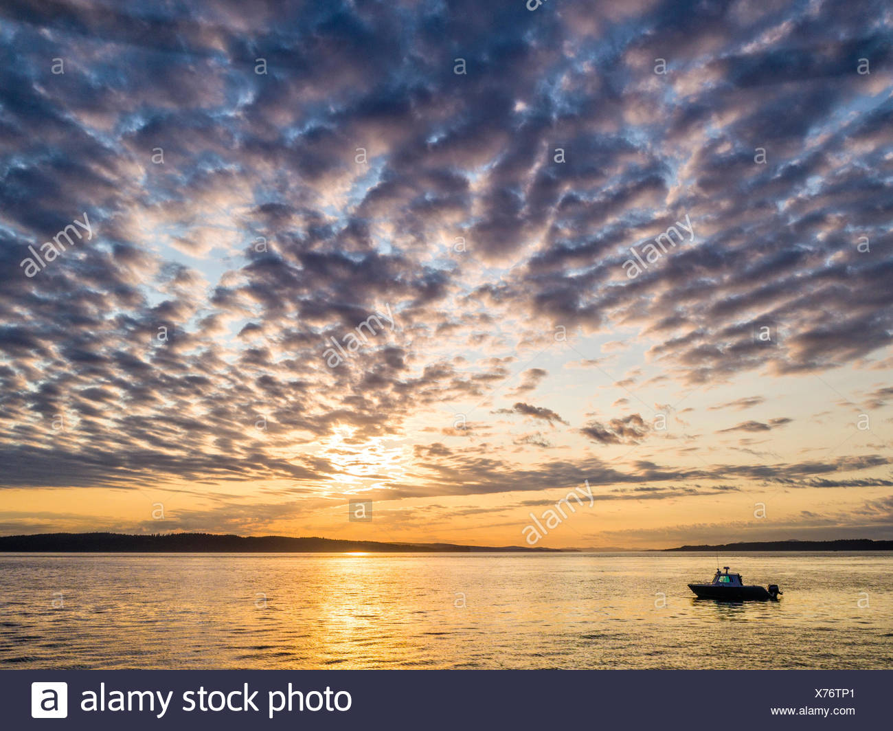 The 'Ambient Light' tour boat (Vancouver Island Photo Tours) during the sunset tour in Weynton Passage off Northern Vancouver Island, British Columbia, Canada - Stock Image
