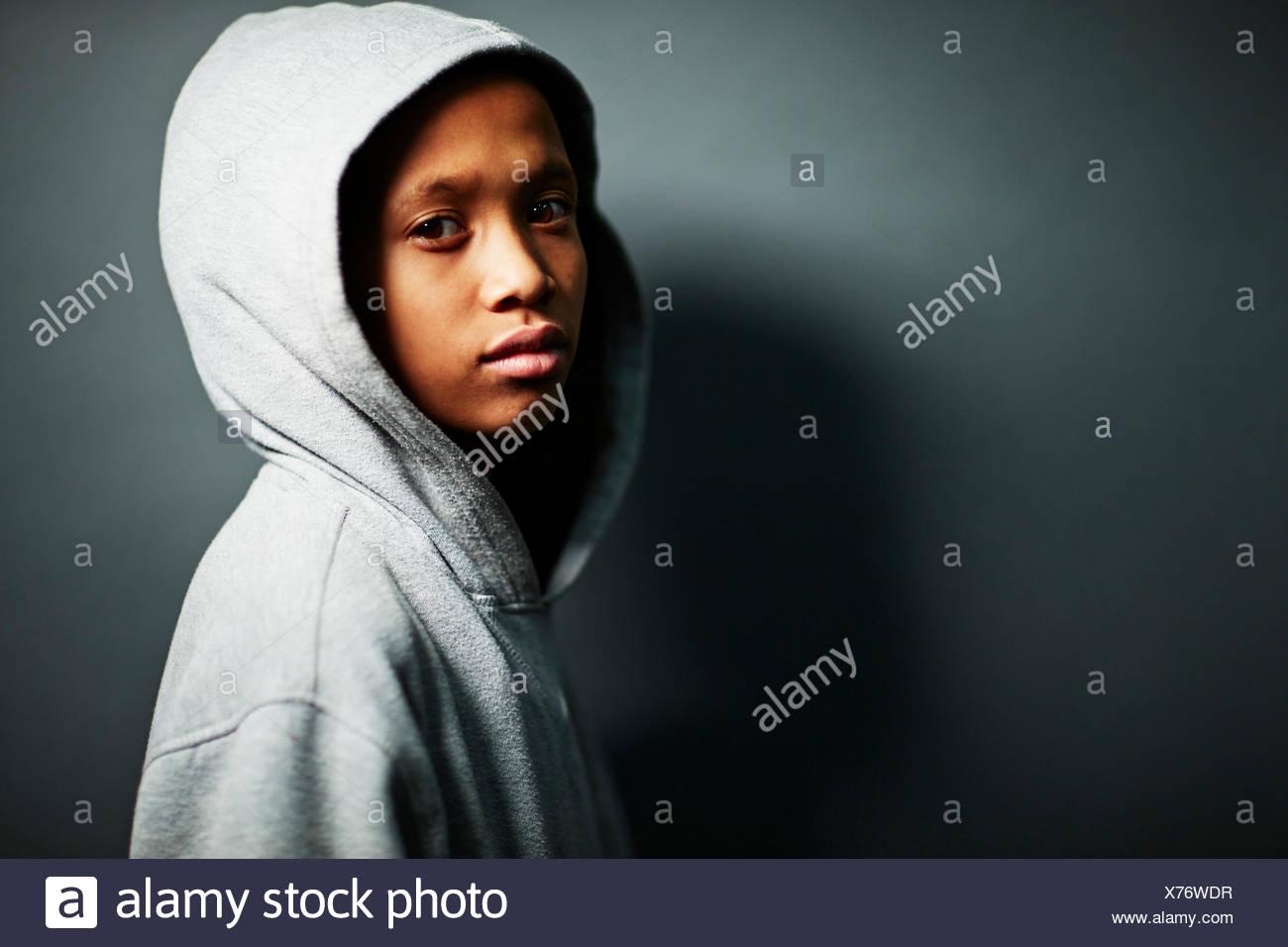 Boy wearing grey hooded top - Stock Image