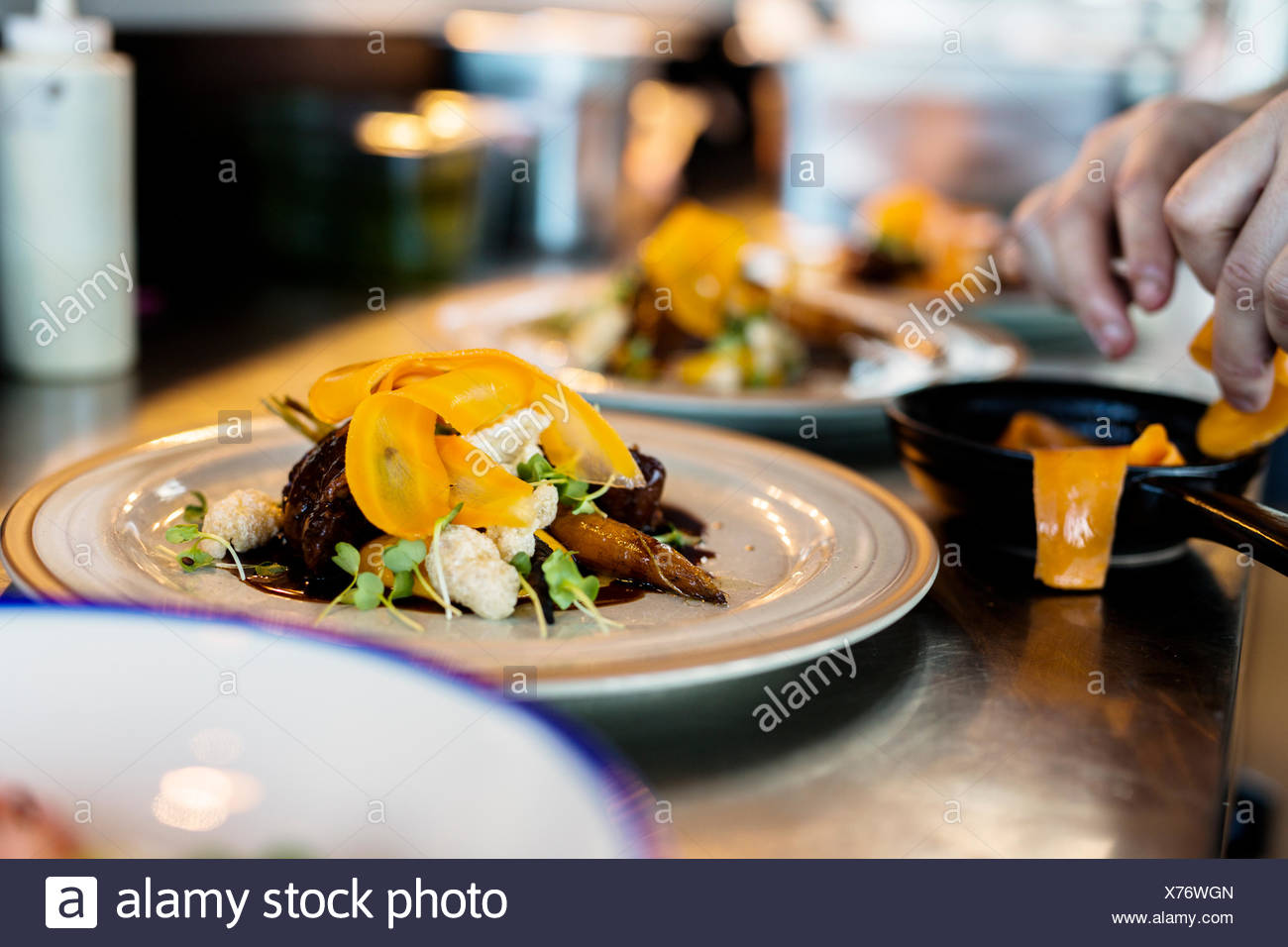 Cropped image of chef preparing dish in Sky bar restaurant - Stock Image