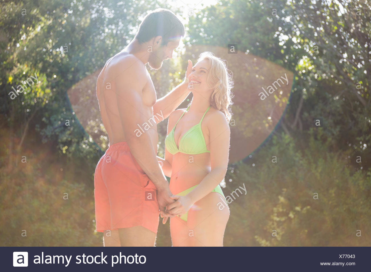 Happy couple in swimwear holding hands and smiling - Stock Image