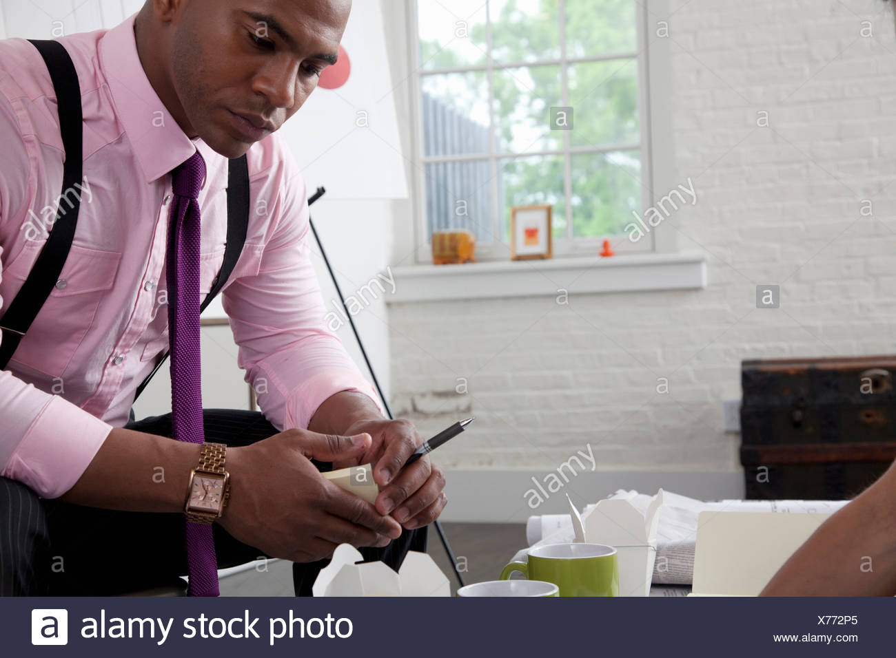 Mid adult office worker looking down at paperwork on table - Stock Image