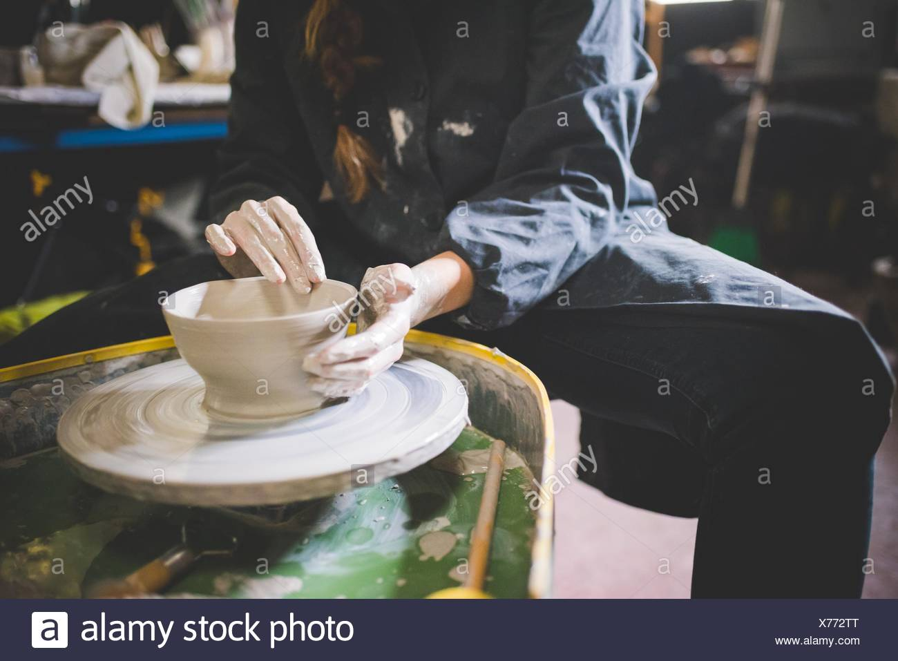 Young woman sitting at pottery wheel making clay pot - Stock Image