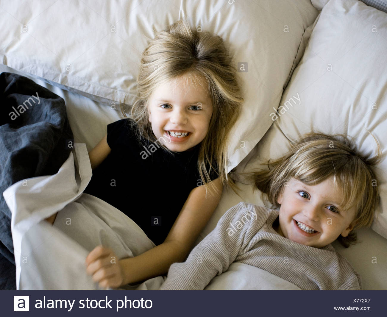 USA, Utah, Provo, Portrait of brother and sister (2-5) lying in bed - Stock Image
