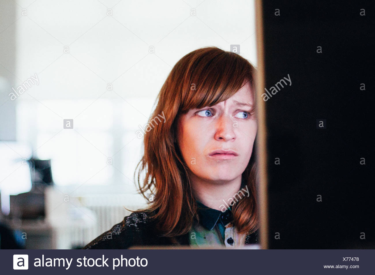 Close-Up Of Worried Woman While Sitting At Computer Desk In Office - Stock Image