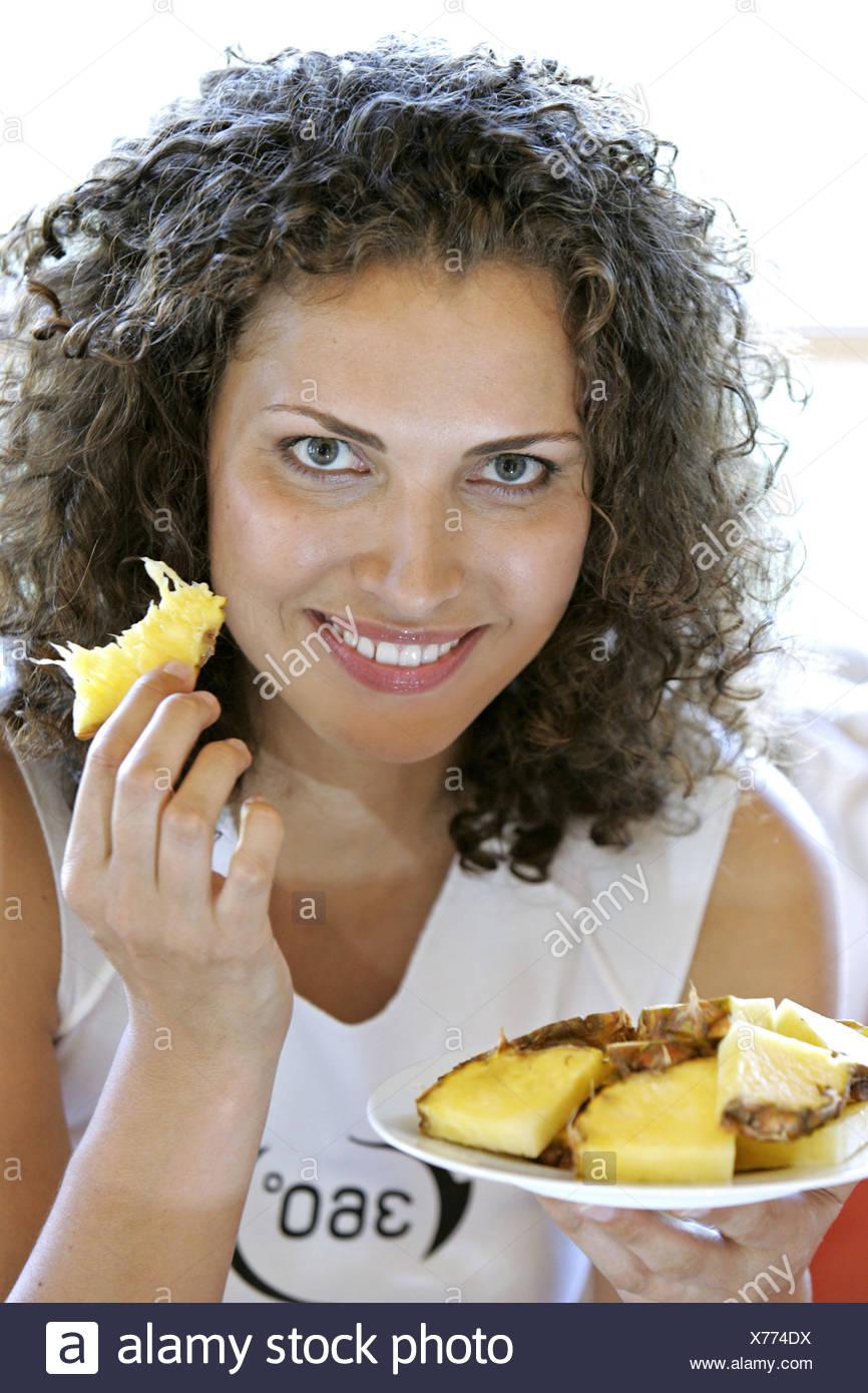 Frau Laecheln Ananas Obst Essen Tropische Frucht Tropical Fruits Portrait innen Frauenportrait Jung Single Natuerlichkeit Zufrie - Stock Image