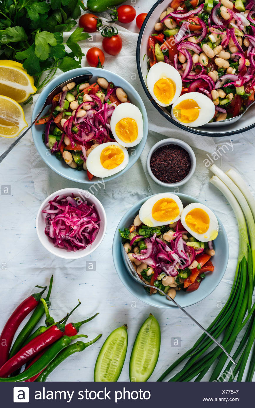 Turkish tangy bean salad known as piyaz served in bowls with halved hard-boiled eggs on the top accompanied by sumac, red onions, peppers, green onion - Stock Image