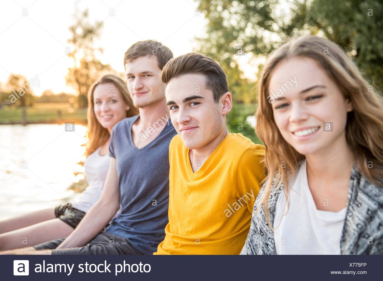 Portrait of group of friends sitting beside lake, smiling Stock Photo