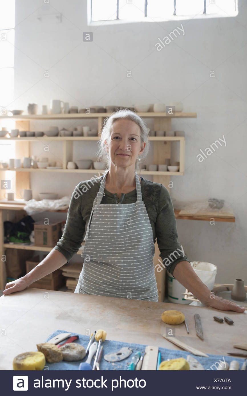 Portrait confident female potter in apron at workbench with tools in art studio - Stock Image