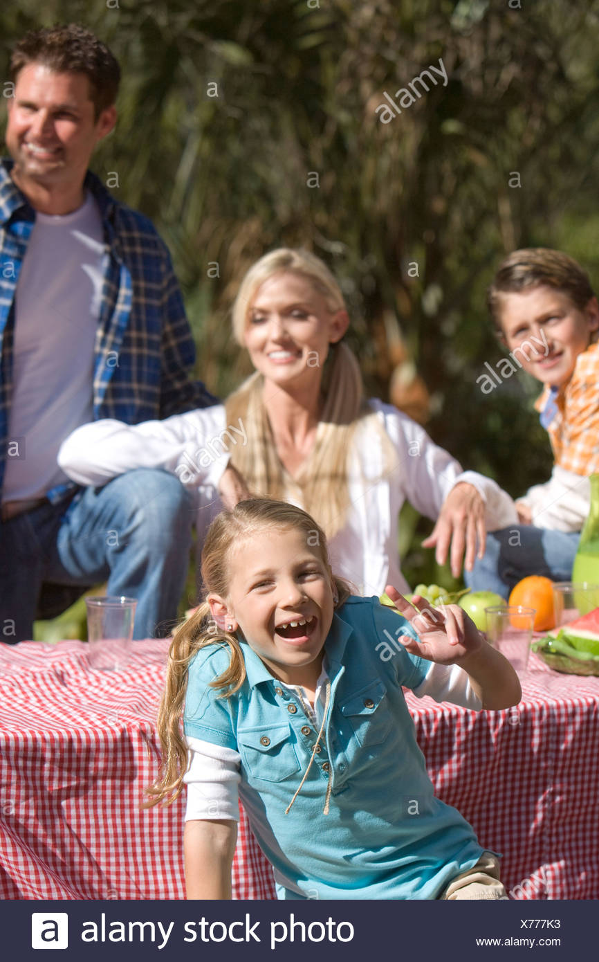 Young girl having fun at picnic table with family in background - Stock Image