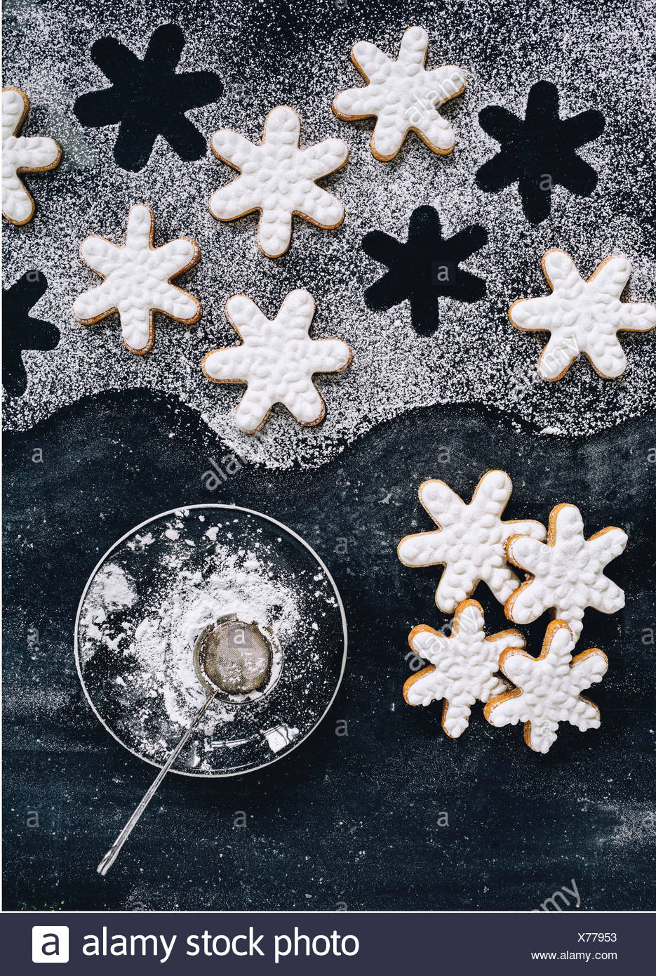 Frosted snowflake cookies and a bowl of powdered sugar. Vertical shot - Stock Image