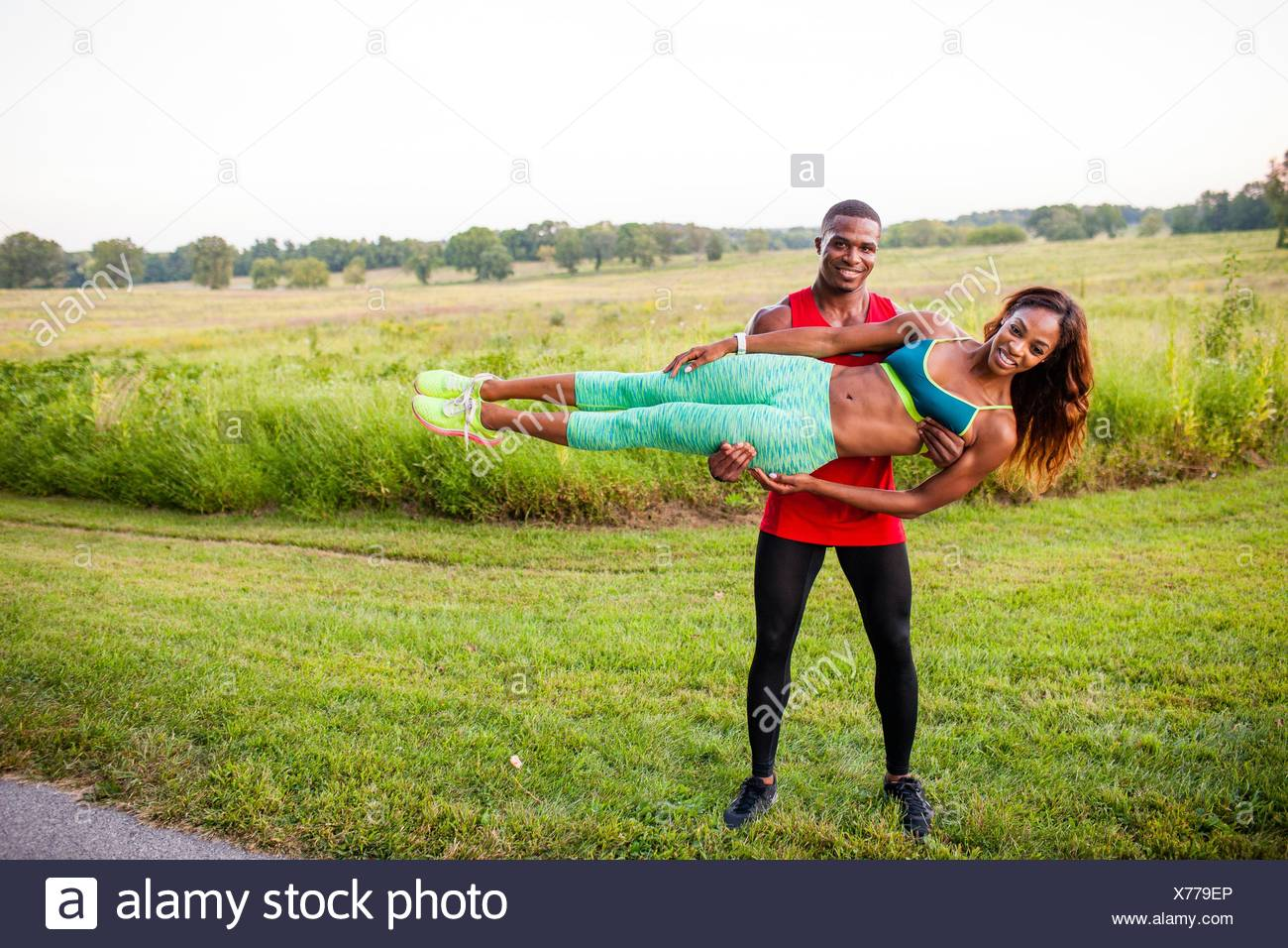 Young man training holding up girlfriend horizontally - Stock Image