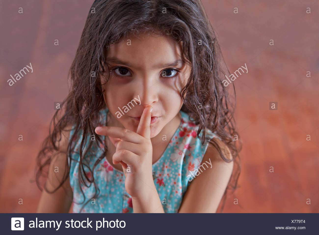 Portrait of girl with finger on lips - Stock Image