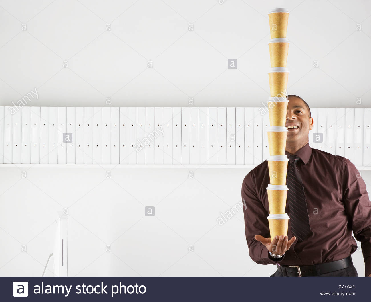 Businessman balancing large stack of paper coffee cups Stock Photo