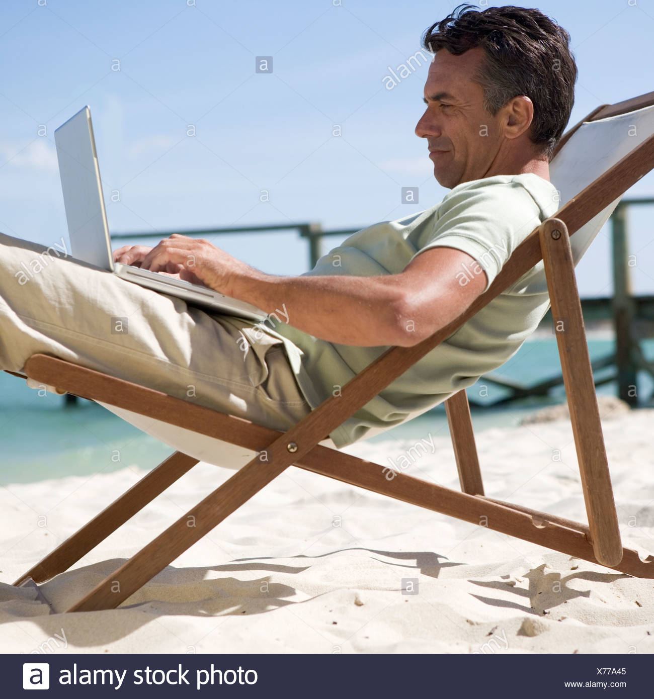 A mature man sitting in a deck chair using a laptop - Stock Image