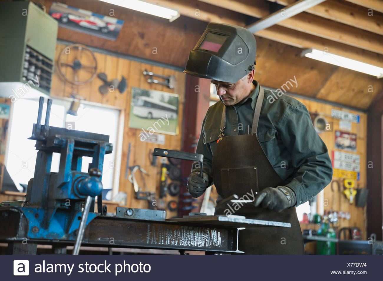 Welder in protective work wear working at workshop - Stock Image