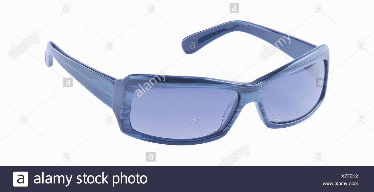 Blue sunglasses against white background, close up - Stock Image