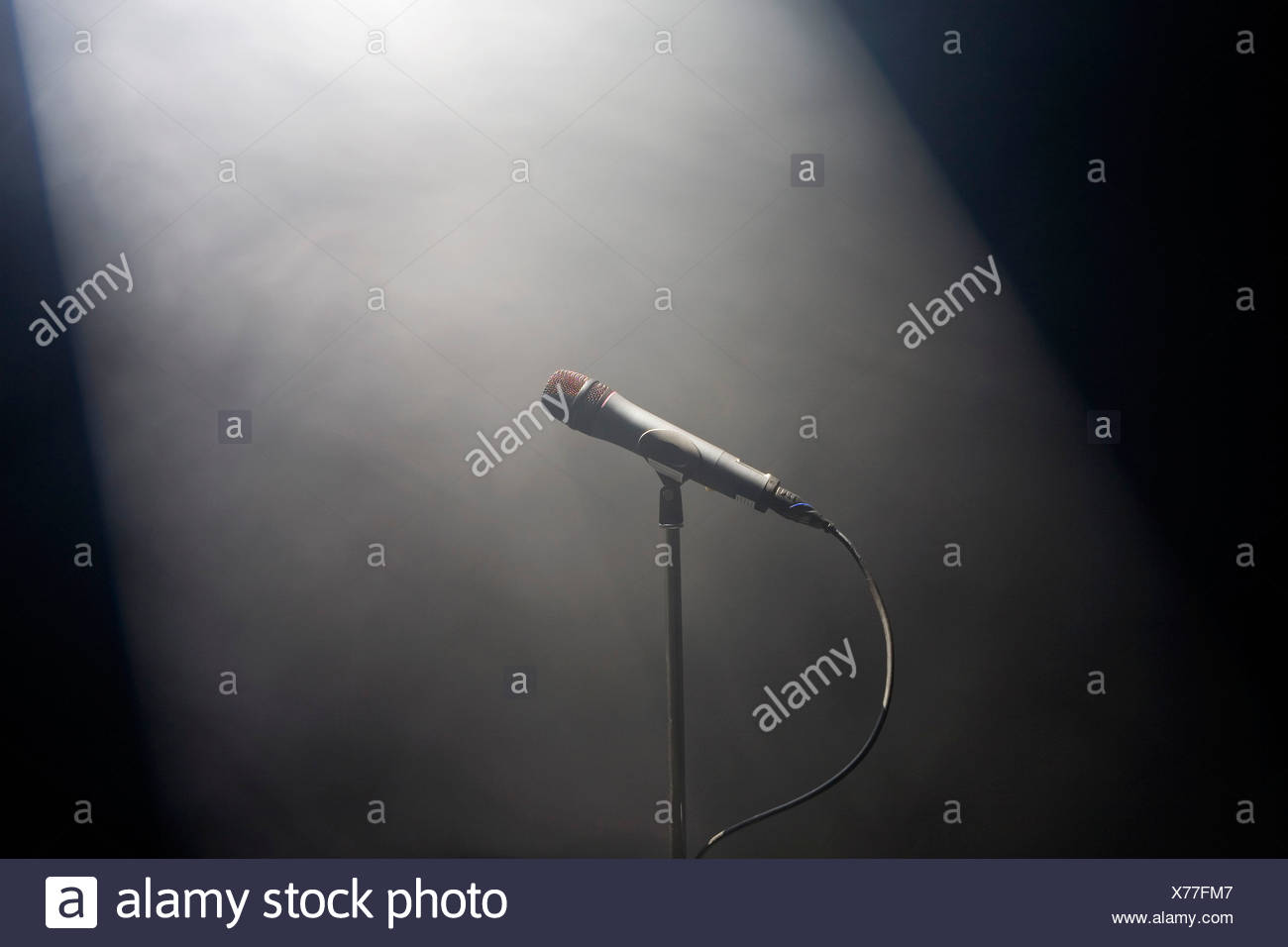 A spot lit microphone stand - Stock Image