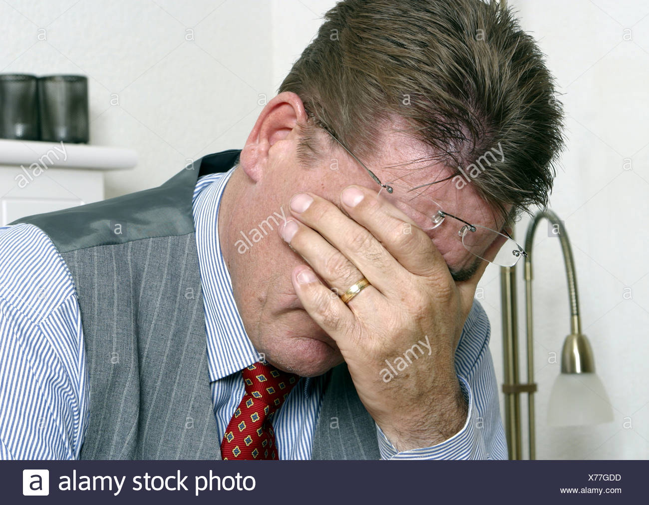 Depressed middle aged man overworked hand covering face - Stock Image