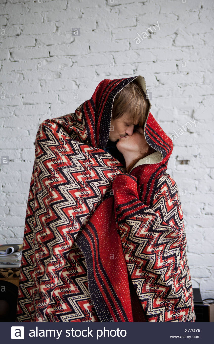 A couple kissing while wrapped in a blanket - Stock Image
