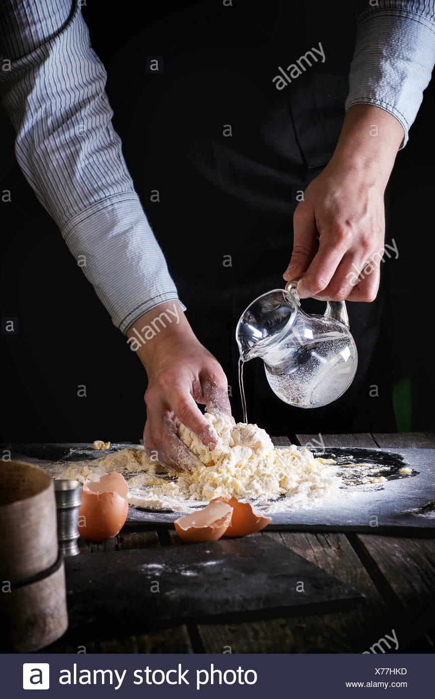 Female hands flowing water from jug, knead the dough for pasta on old wooden kitchen table. Broken eggs at foreground. Dark rust - Stock Image