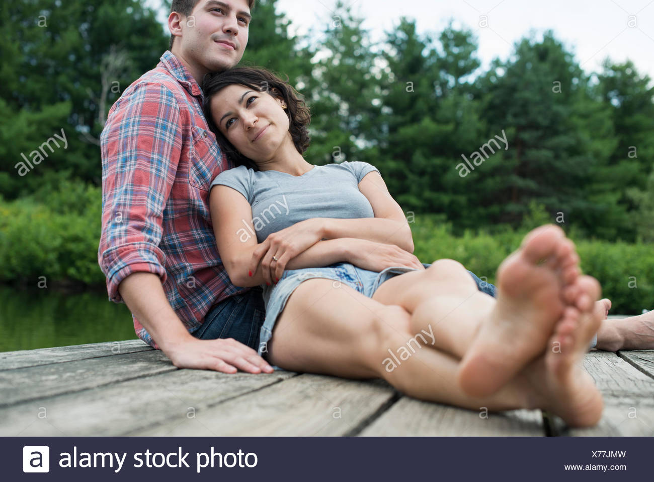 A couple relaxing on a jetty overlooking a mountain lake. - Stock Image