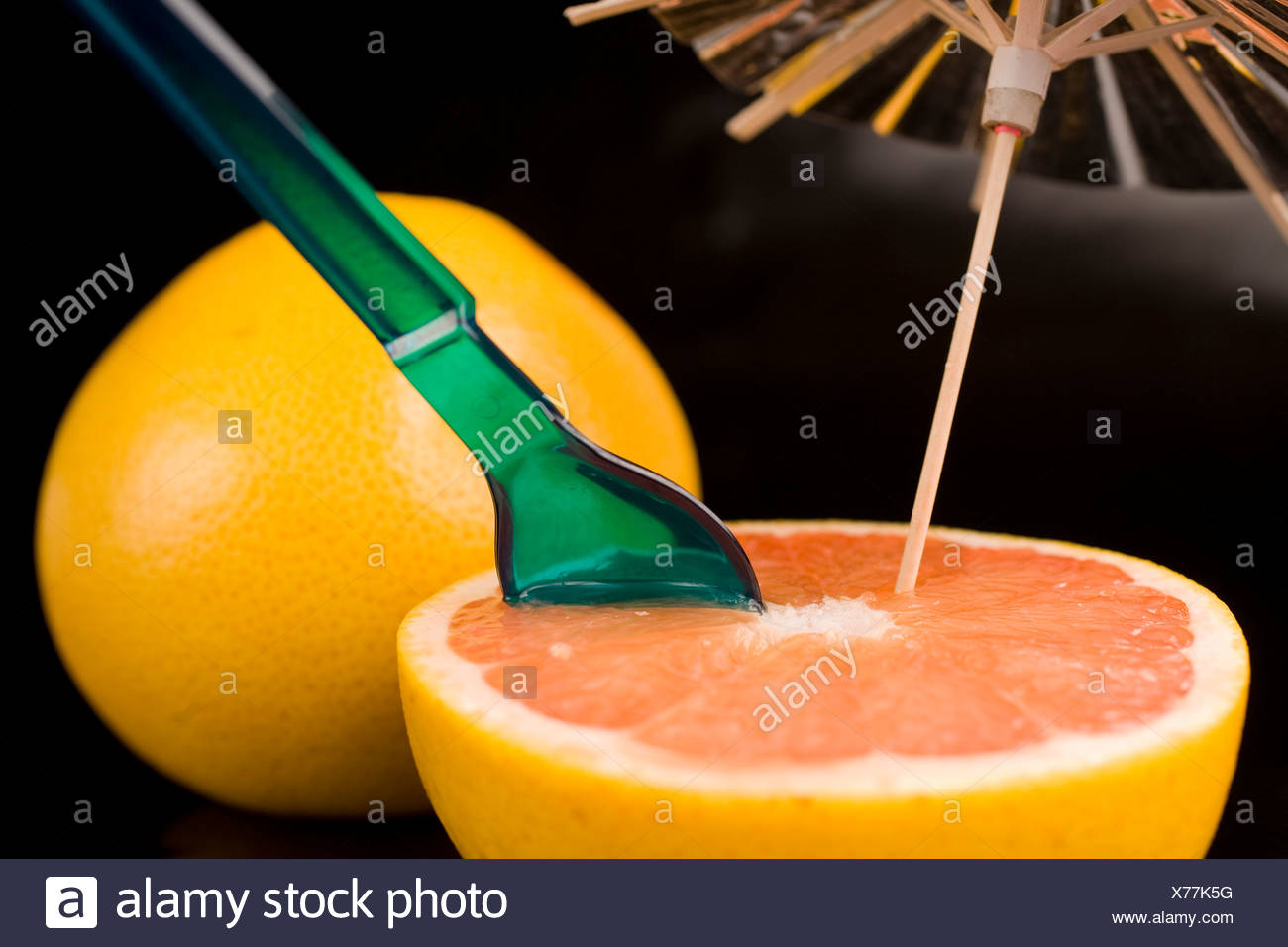 Close-up of a spoon in grapefruit slice by a whole grapefruit against dark background - Stock Image