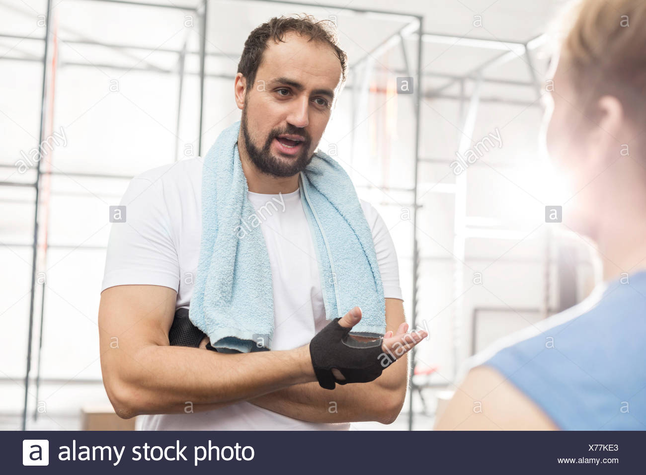 Man talking to male friend in crossfit gym - Stock Image