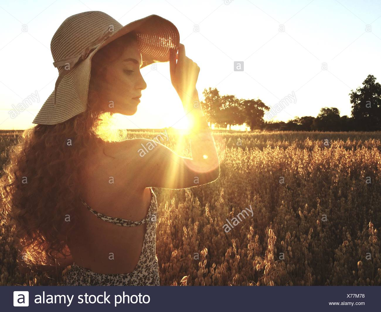 Beautiful Woman Standing On Field Against Clear Sky During Sunset - Stock Image