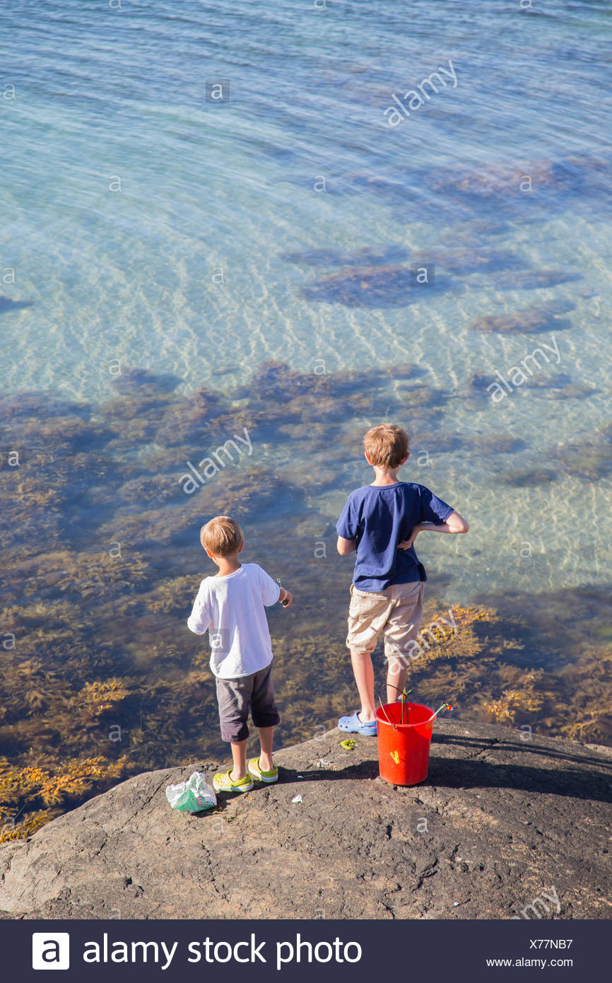 Children (6-7, 12-13) playing by sea - Stock Image