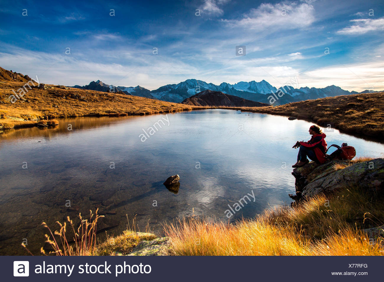 A hiker enjoying the first daylights in front of the landscape of Adamello-Presanella - Tonale mount, Lombardy, Italy. Europe - Stock Image