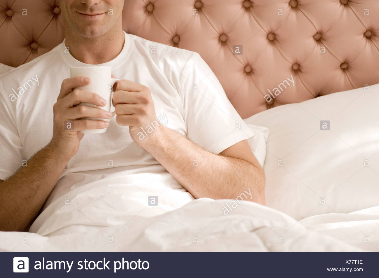 Young man holding a cup while relaxing in bed - Stock Image