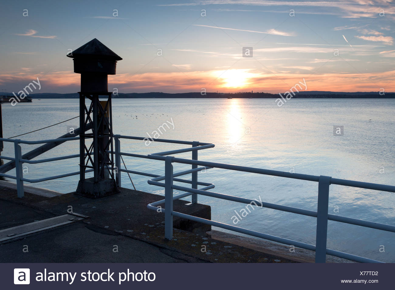 Old fog horn on the pier in Meersburg on Lake Constance, overlooking the lake towards Konstanz at sunset, Baden-Wuerttemberg - Stock Image