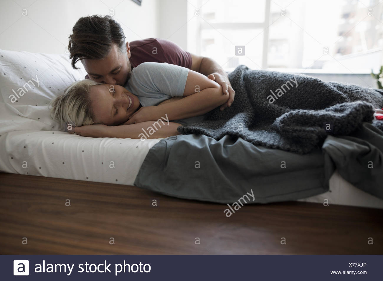 Affectionate,romantic couple kissing and cuddling in bed - Stock Image