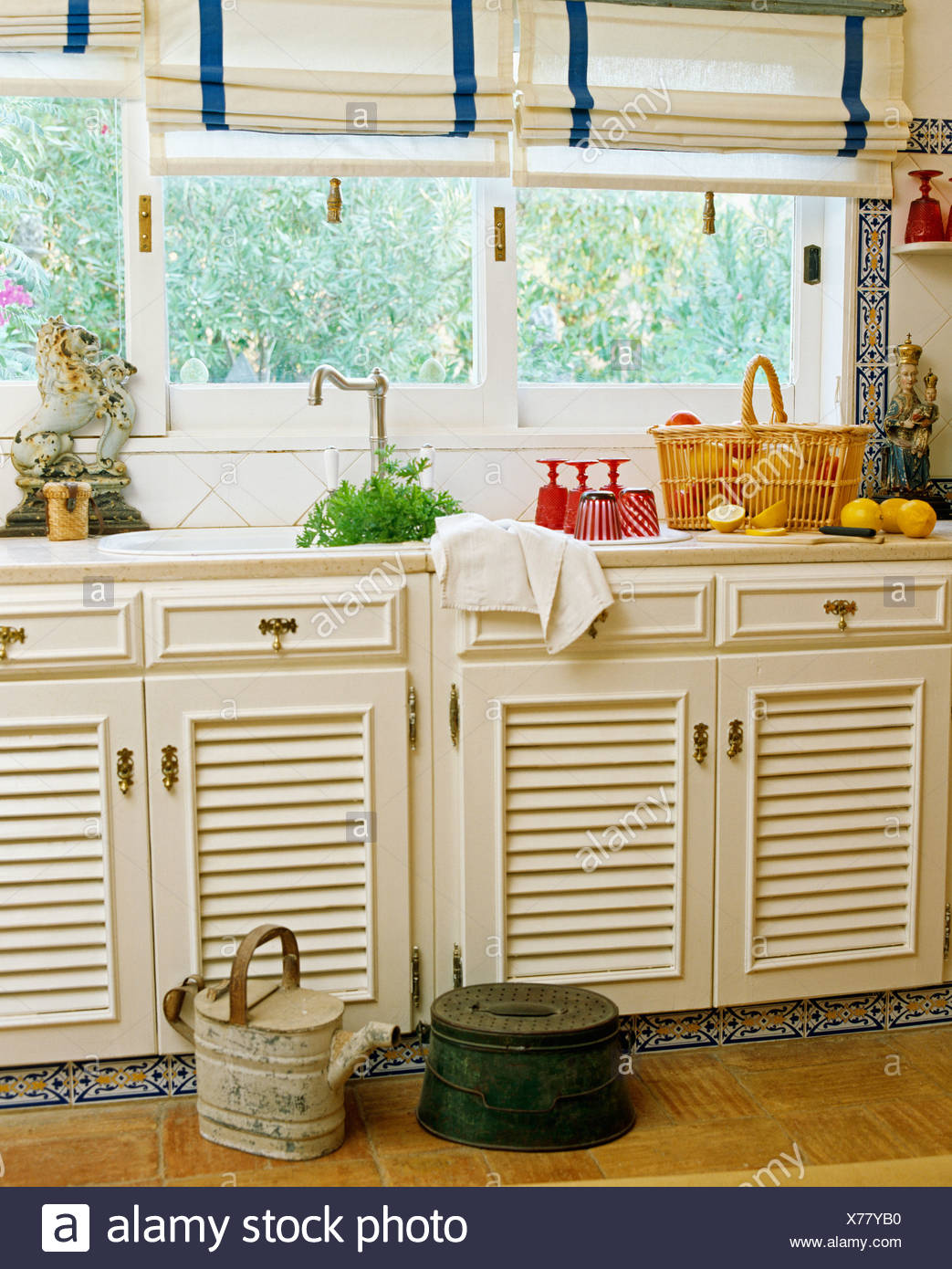 White Linen Blinds On Window Above Sink In White Portuguese Kitchen With Louvre Doors On Fitted Cupboards Stock Photo Alamy