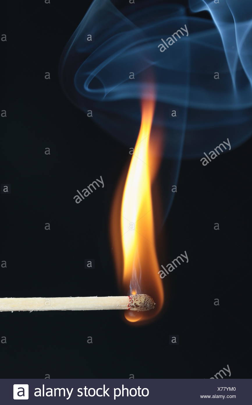 ignited match with blue smoke on black background Stock Photo