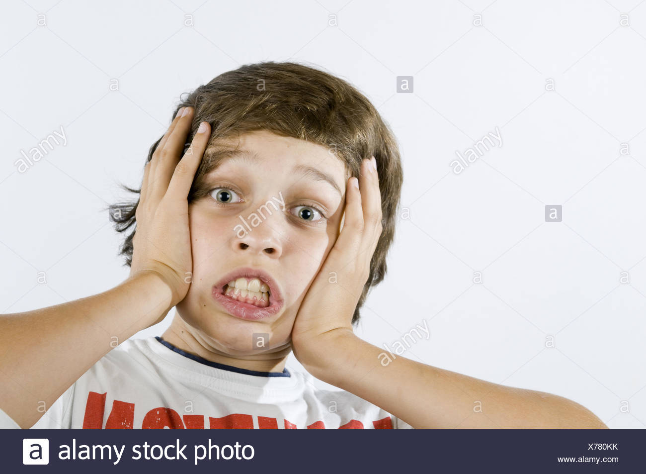 fearful grimacing of boy on white - Stock Image