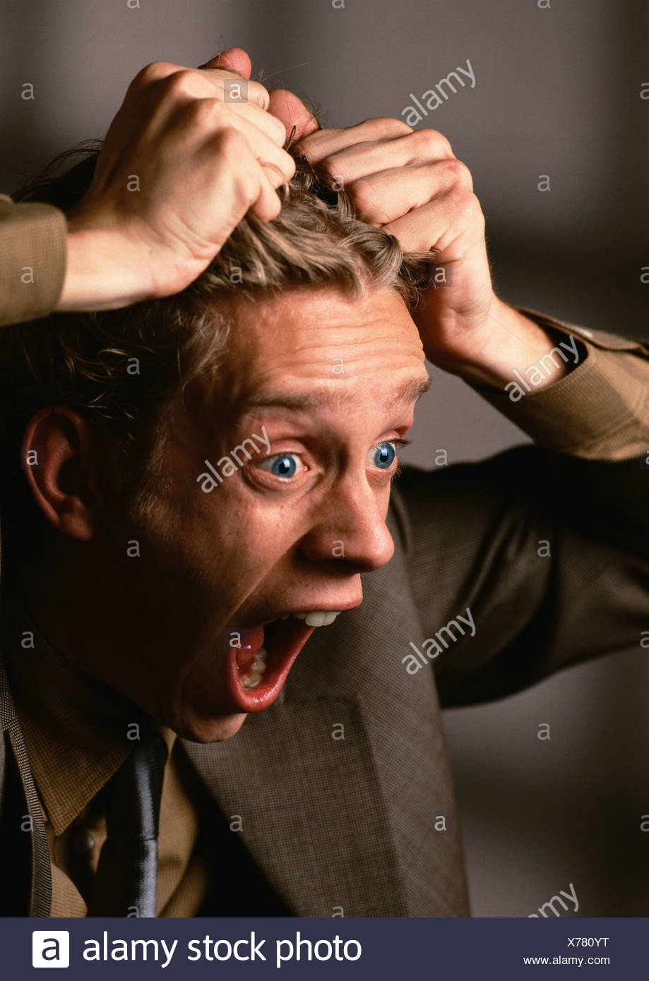 Man with mouth and eyes wide open, pulling hair, close-up - Stock Image