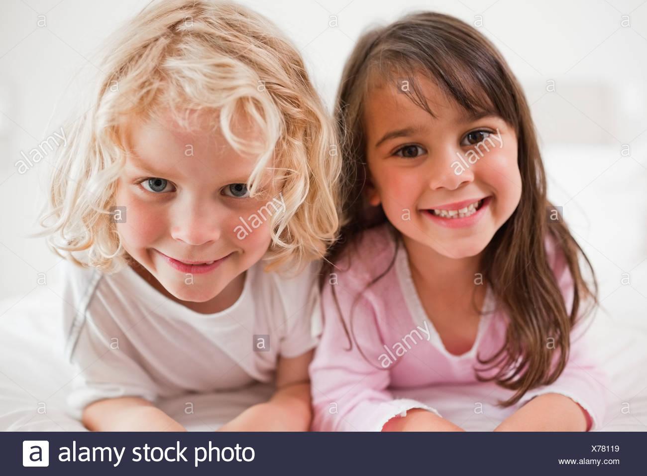 Siblings lying on their bellies - Stock Image