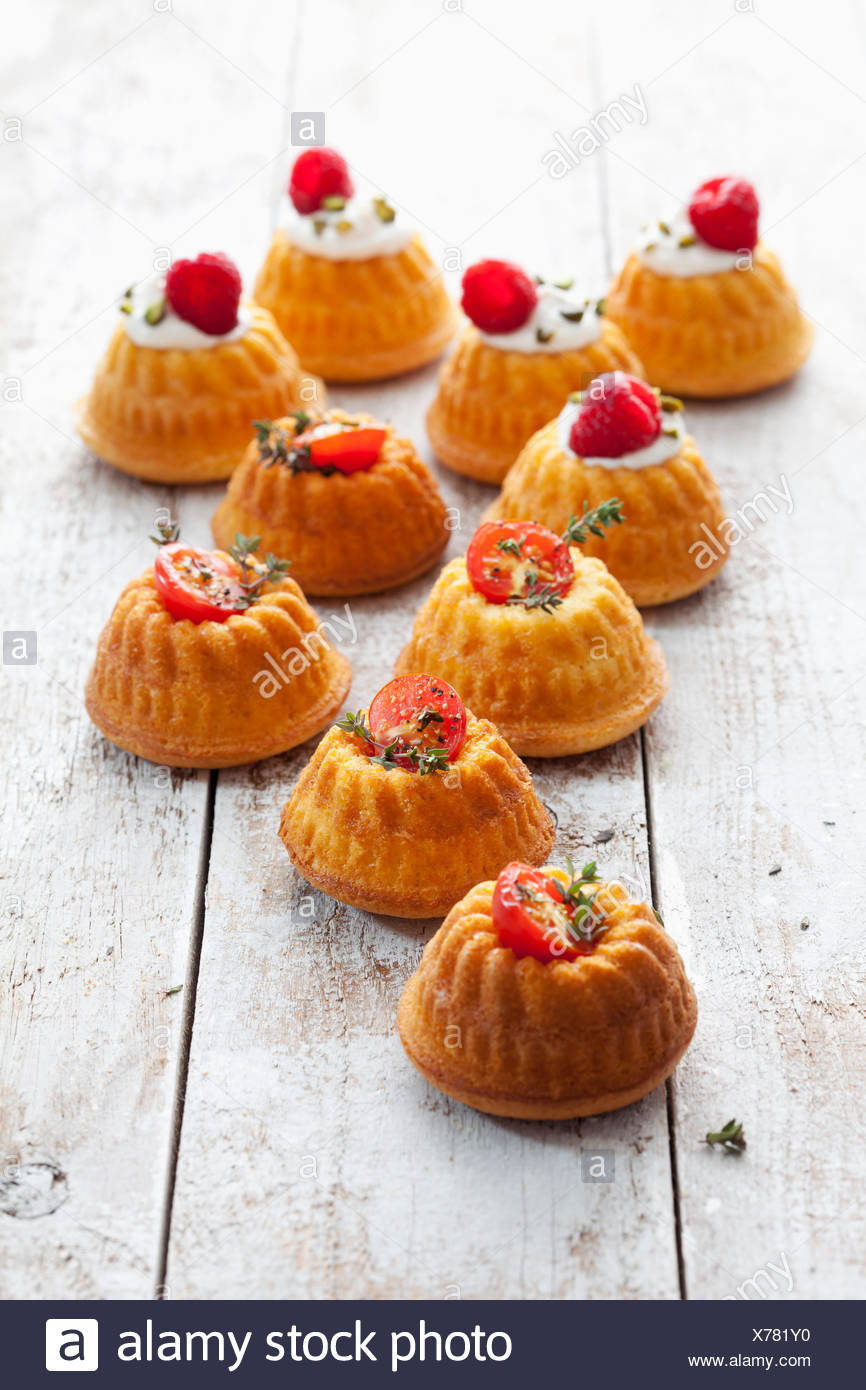 Mini Gugelhupf filled with cream cheese and ricotta garnished with tomato and marjoram or raspberry and pistachio Stock Photo