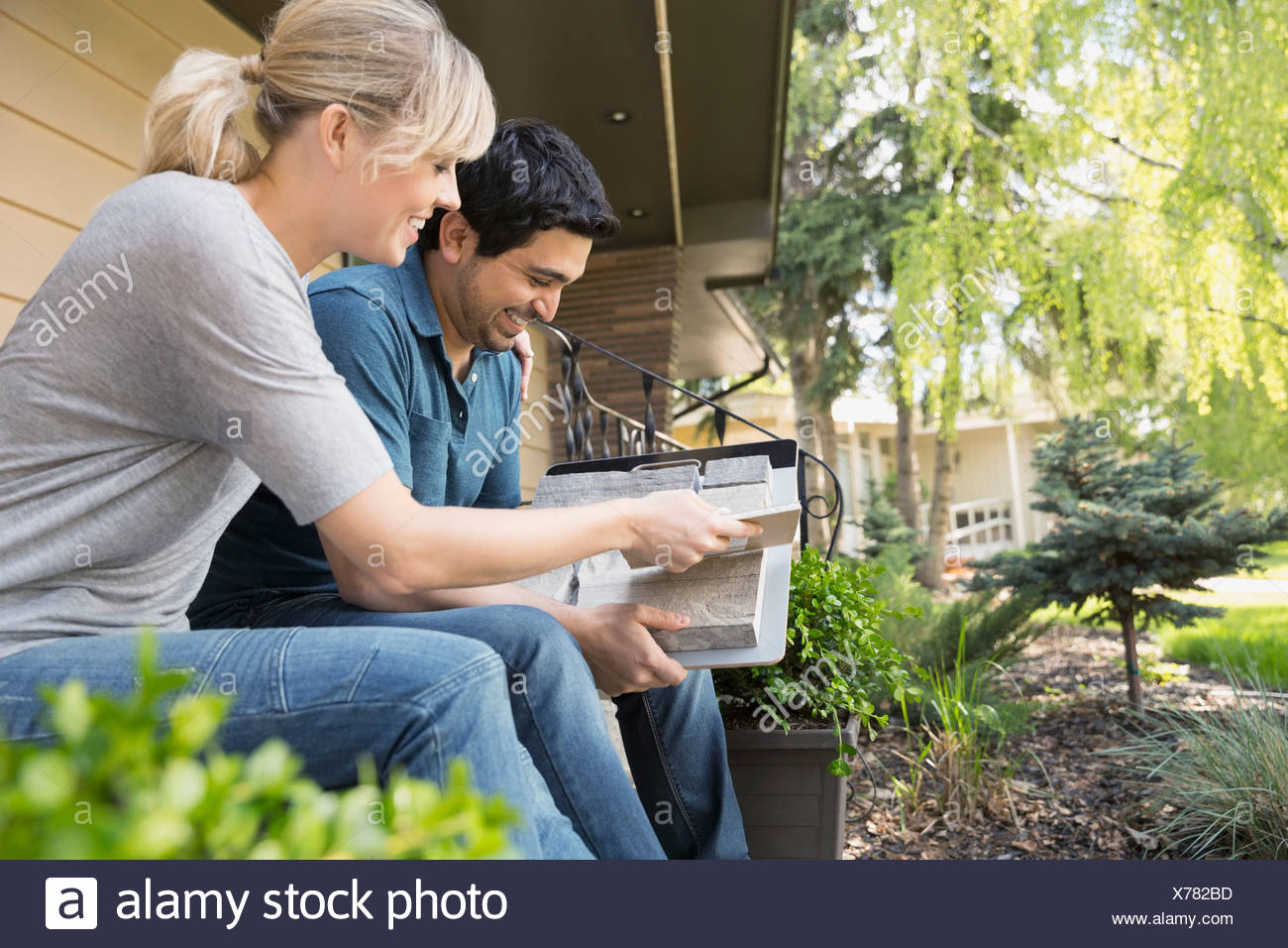 Couple looking at granite swatches on front stoop - Stock Image
