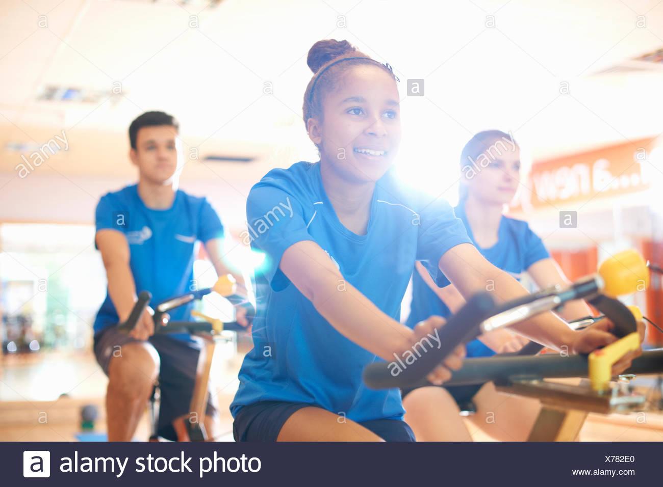 Young woman on exercise bike - Stock Image