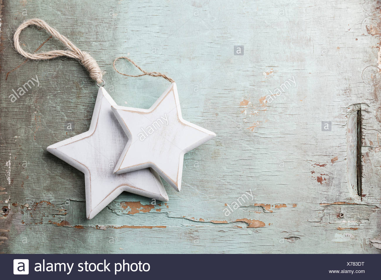 Wooden Christmas decorations stars on blue textured background - Stock Image