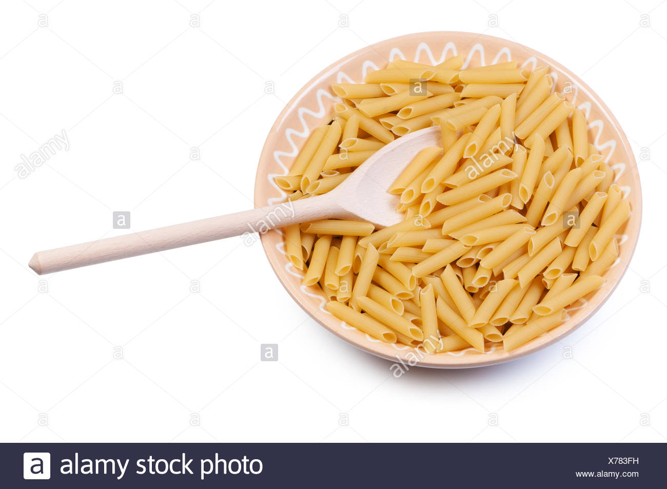 Plate with raw pasta and wooden spoon on white background. - Stock Image