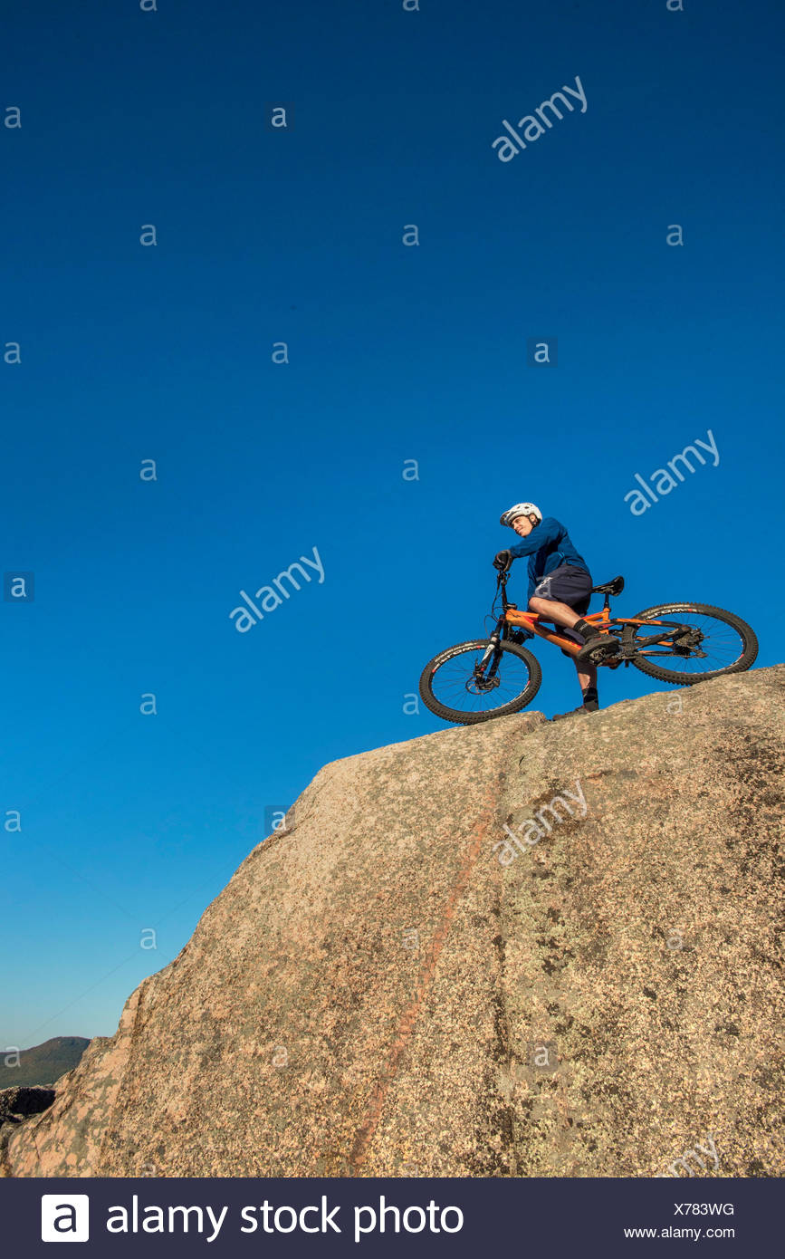 Low Angle View Of Alex Leich With Mountain Bike On The Bare Granite Slabs In North Conway, New Hampshire - Stock Image