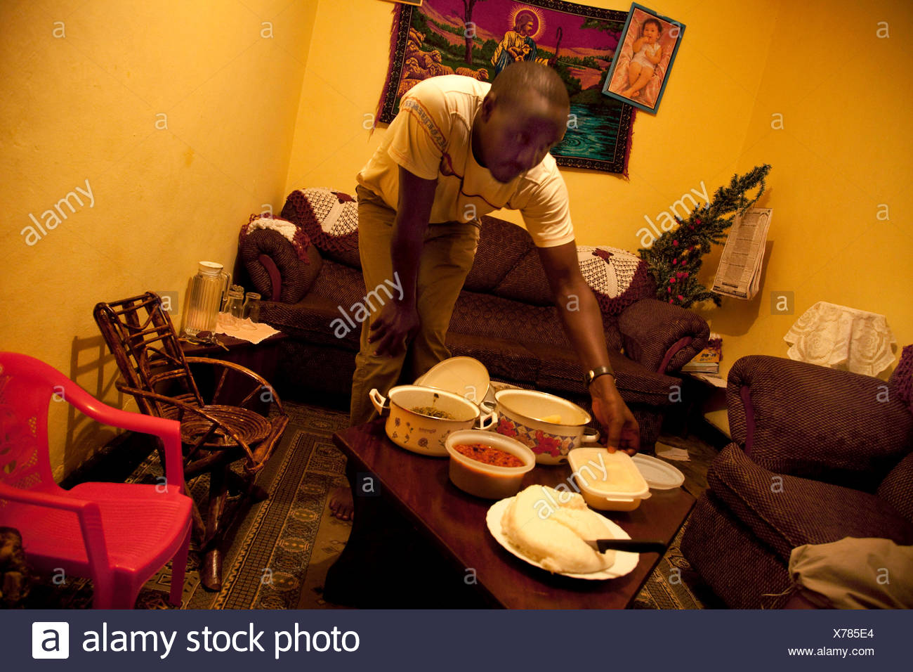 Man putting food on the table in a christian household, christian brodery on the wall in the background, Rwanda, Nyamirambo, Kigali - Stock Image